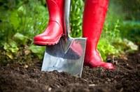 Moestuin met spade en rode laarzen